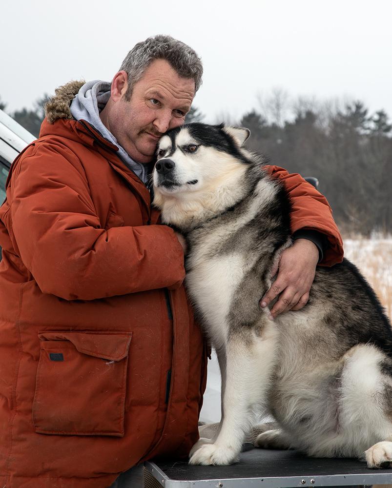 Owner Mark Reisner cuddling sled dog