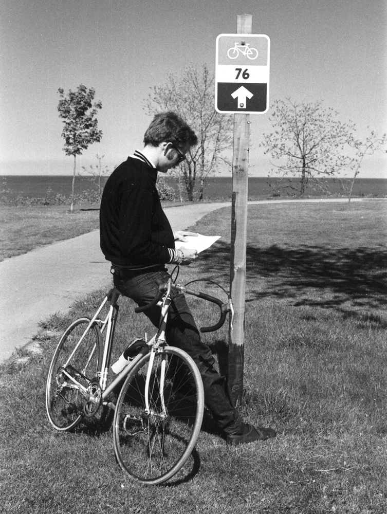 man leaning on bike reading