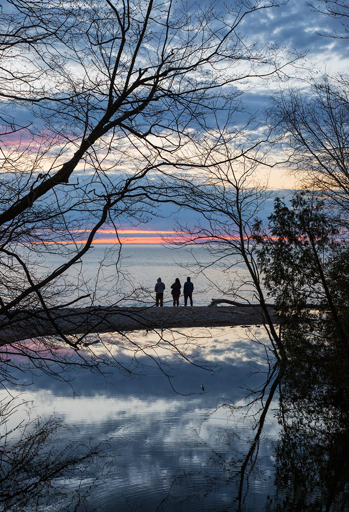 Three people on Lake Michign beach at sunrise