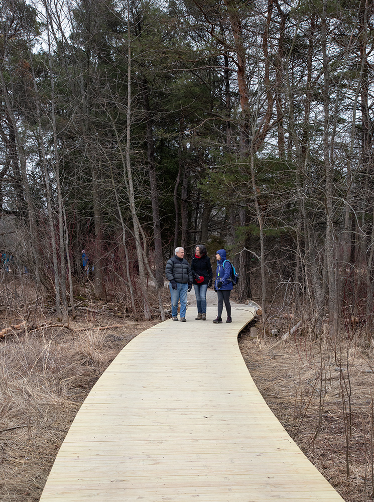 three people walking along a boardwalk