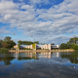 the Washington Park branch of the Urban Ecology Center with clouds reflecting in the lagoon