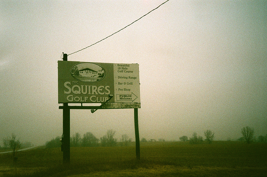 "Billboard reading ""Squires Golf Club"" in fog"