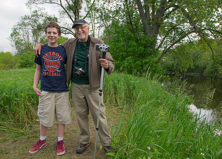 Artist in residence Hal Rammel and camera with a teenage boy next to Milwaukee River