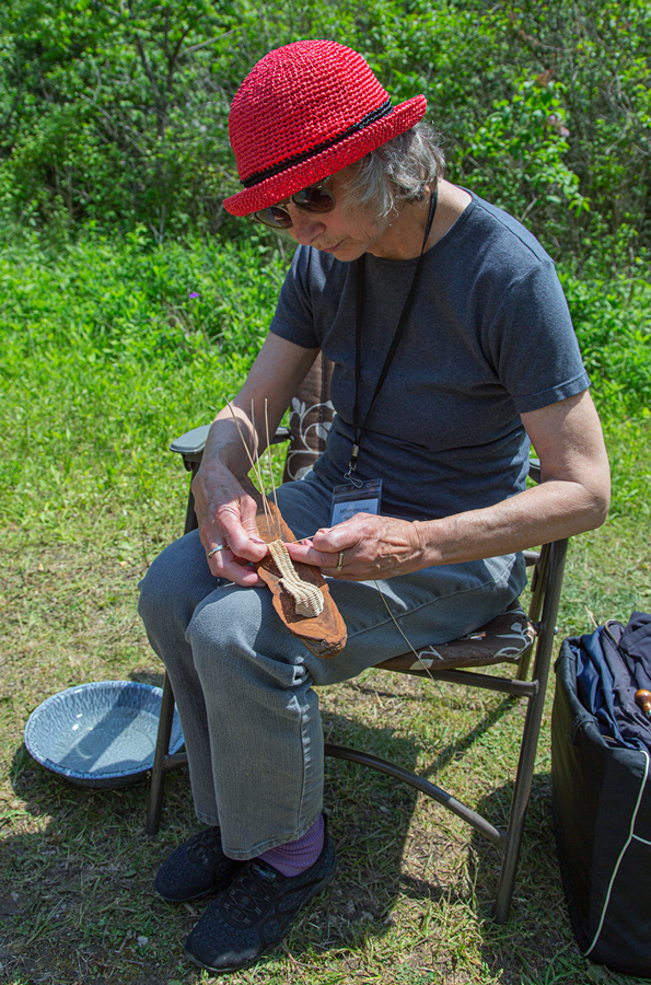 Artist in residence Rise Andersen working on a demonstration piece using basketry techniques on a wooden plaque