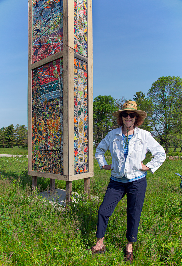 Artist Sally Duback with her colorful art installation, which functions as a chimney swift tower