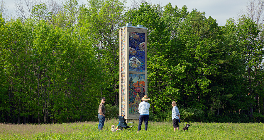 three people around artistic chimney swift tower with ceramic murals on it