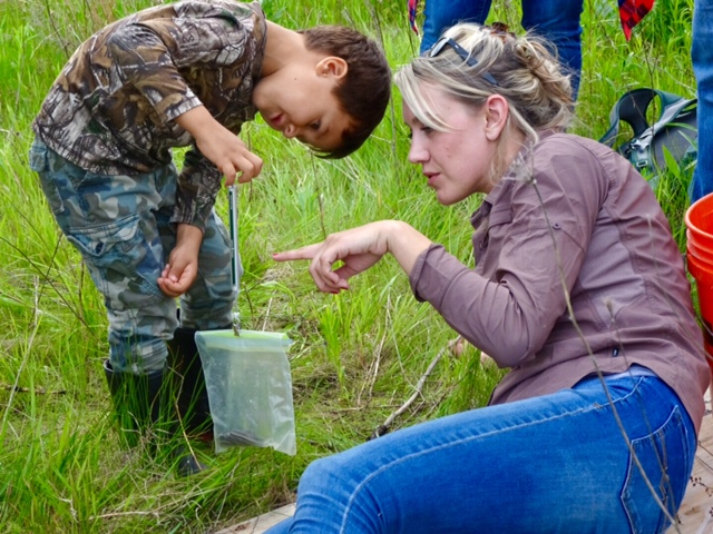 Julia Robson assists a young scientist in determining the mass of a snake.