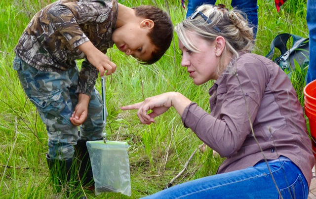 Conservation Biologist Julia Robson shows a boy how to measure the weight of a snake using a plastic bag