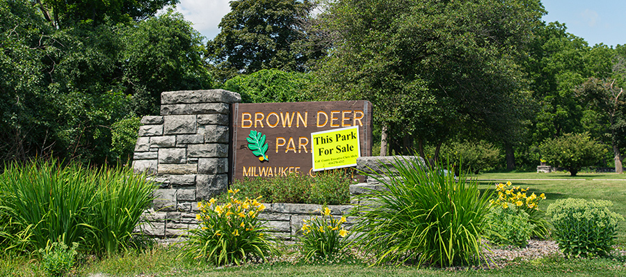 "Brown Deer Park sign with a ""This Park For Sale"" sign attached"