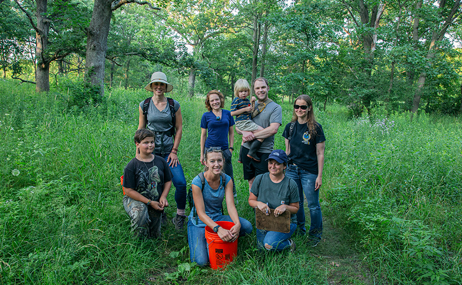 six adults and two children citizen scientists on a trail in a woodland