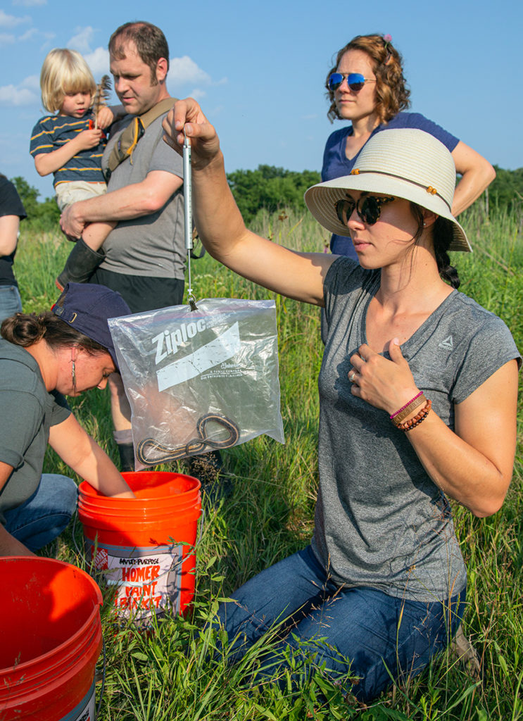 A woman in a hat weighing a garter snake as others look on