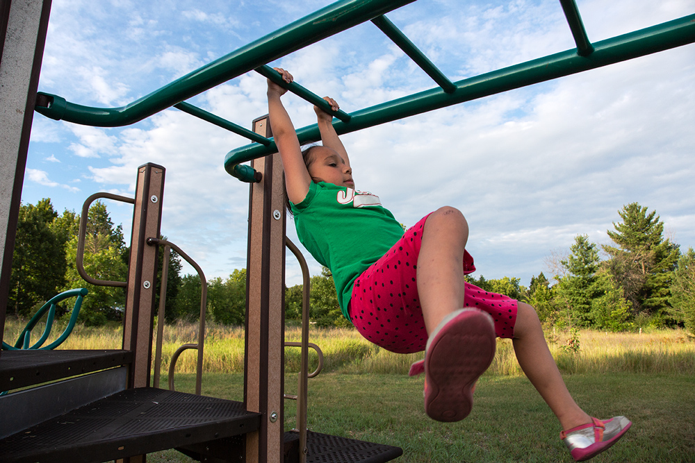 a girl swinging on a playground structure
