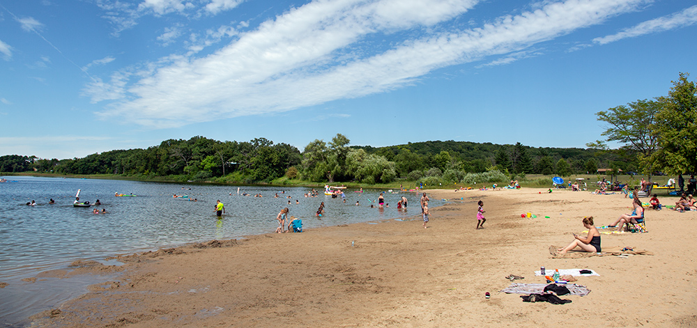 sandy beach at a lake with people sitting and bathing