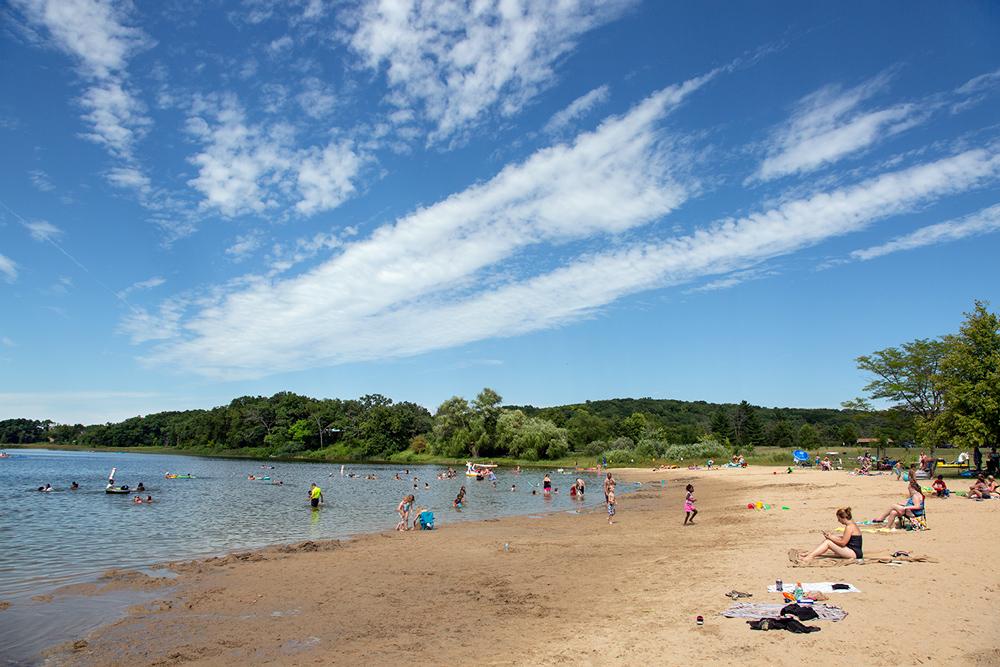 Ottawa Lake beach with bathers and a dramatic sky