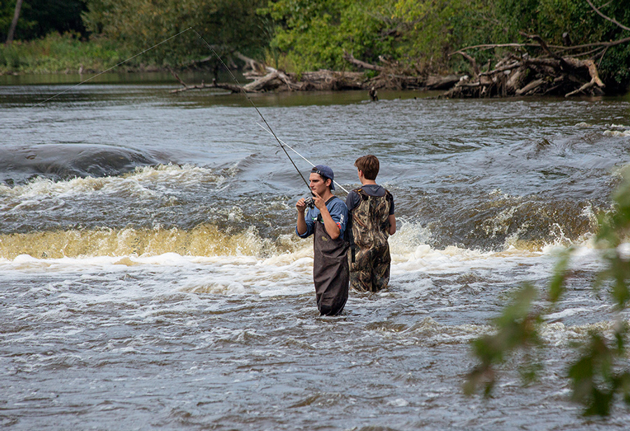 two young men in hip waders fishing below the falls in the Milwaukee River