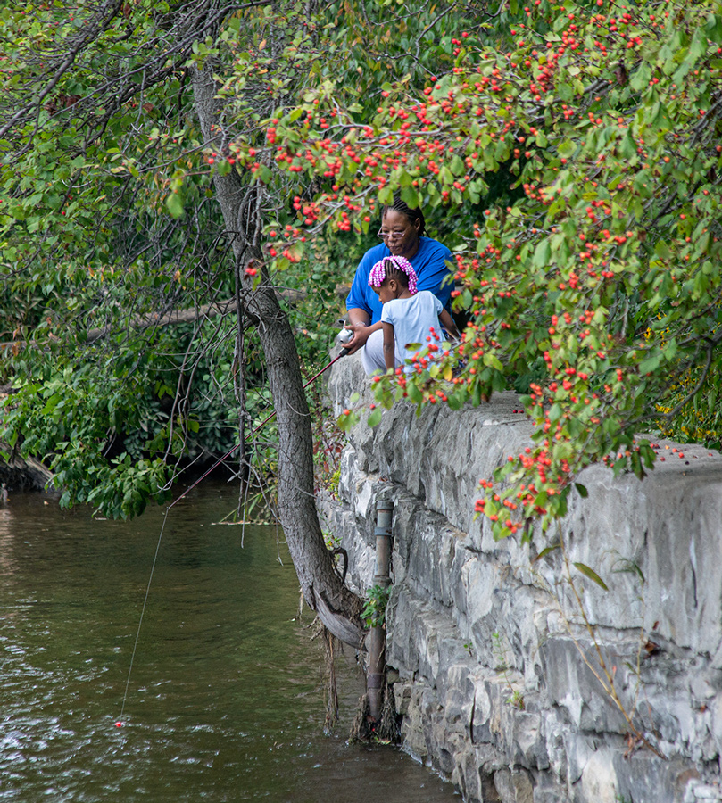 A woman and a young girl sitting on a rock wall, fishing in the Milwaukee River, with red berries overhanging them