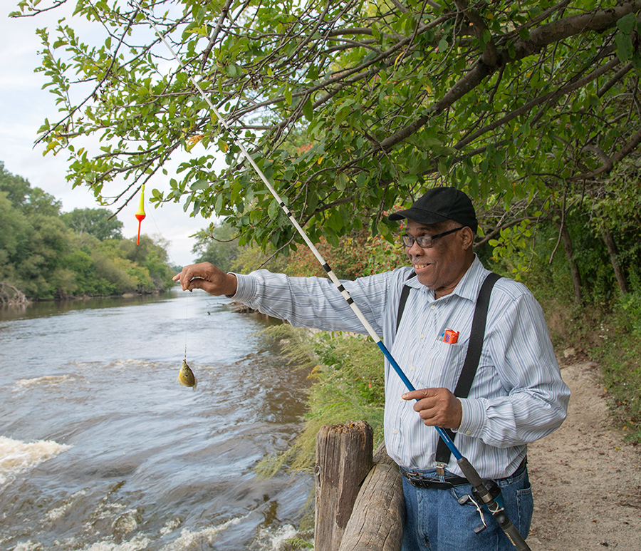 man holding up a fishing rod with a small bluegill attached, next to the Milwaukee River