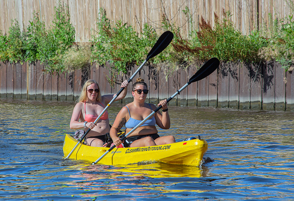 two young women in a two-person kayak paddling next to a steel floodwall on the Milwaukee River.