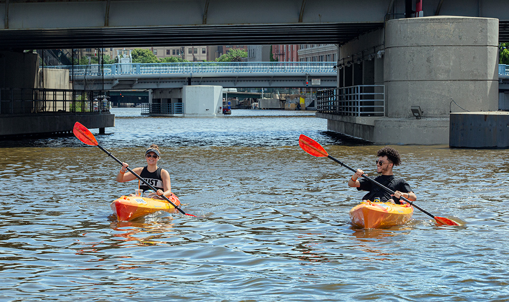 two kayaks paddling in tandem with bridges in the background on the Milwaukee River.