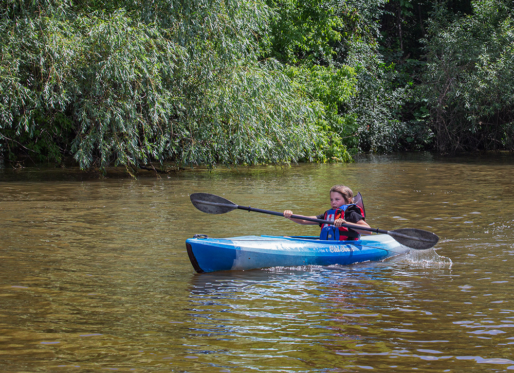 a boy in a kayak with a large paddle next to a wooded shoreline on the Milwaukee River.