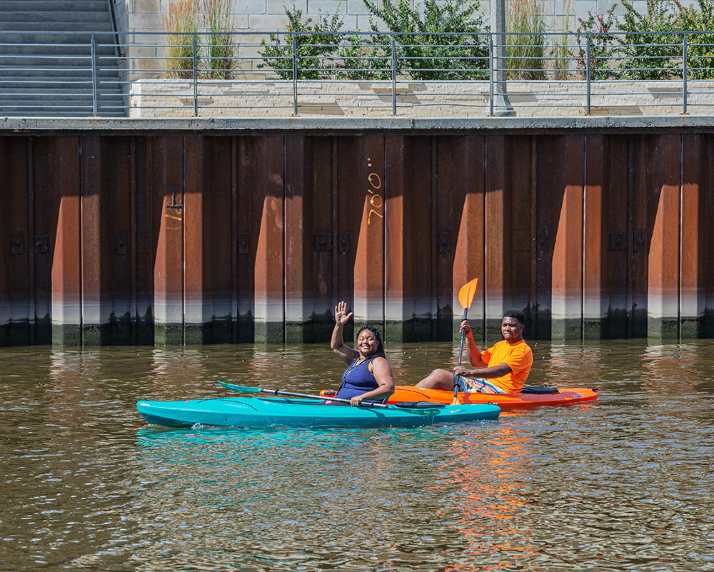 two kayakers, one waving, paddlng next to a steel flood wall on the Milwaukee River.