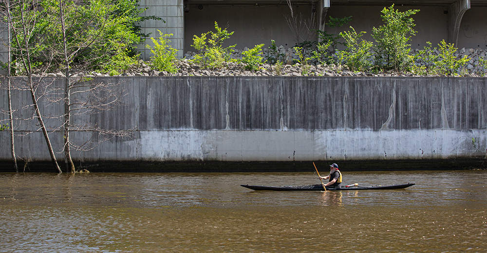 A kayaker paddling next to a concrete flood wall on the Milwaukee RIver