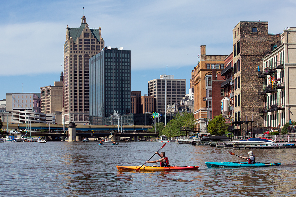 two kayaks on the Milwaukee River with downtown buildings in the background