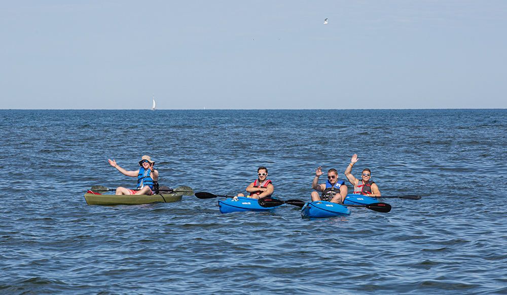 four men in kayaks floating out in the middle of Lake Michigan and waving