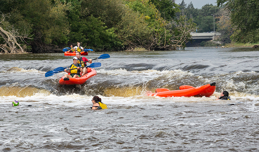 a raft going over the falls on the Milwaukee River as another raft waits and one is capsized under the falls