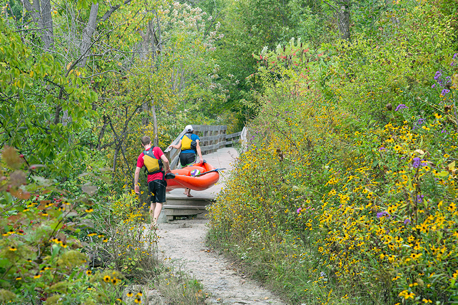 two young people portaging a red rubber raft on a boardwalk trail alongside the Milwaukee River