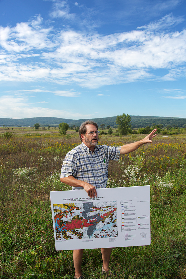 A man with a graphic map standing on a prairie with a low mountain range in the background