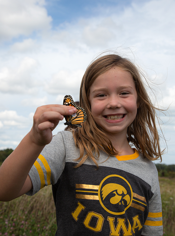 girl with a big smile holding a tagged monarch butterfly by the wings