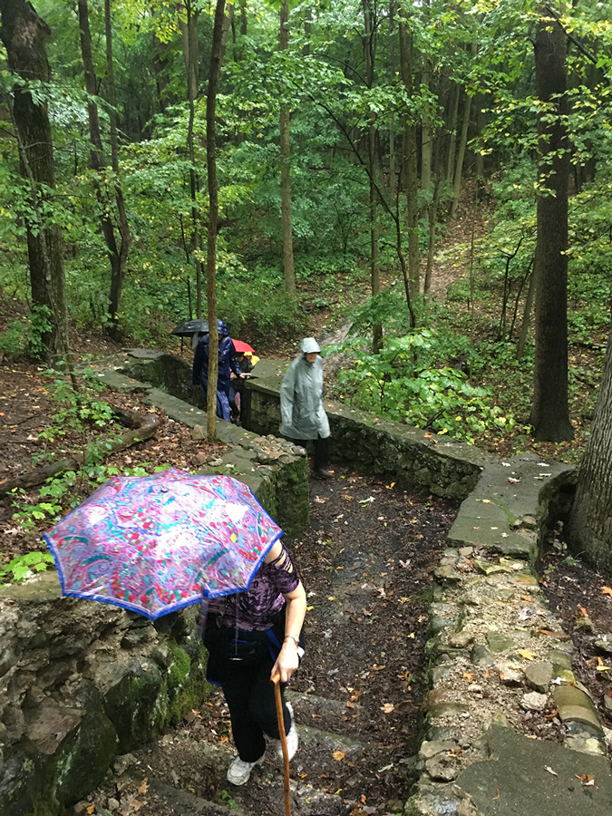hikers walking up a staircase ruin in Sanctuary Woods