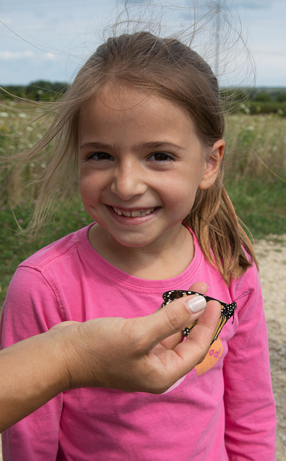 a young girl with a smile as a hand holds out a monarch butterfly
