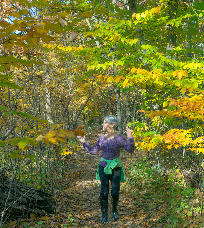 a woman expressing joy at being in the beautiful autumn woods