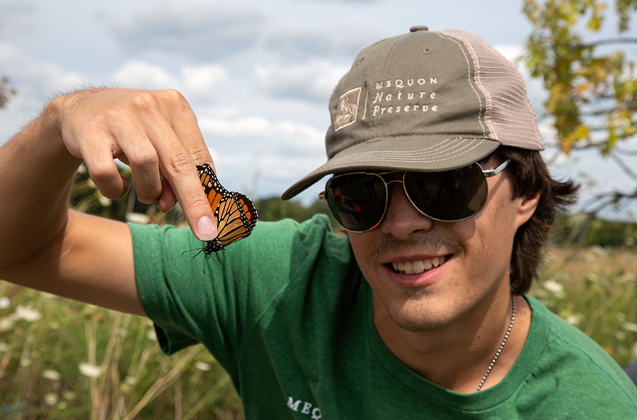 a man with a baseball cap and sunglasses holding a monarch butterfly