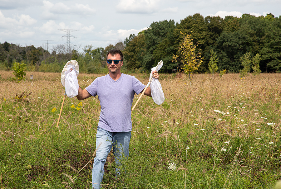 a man holding up two nets that contain monarch butterflies