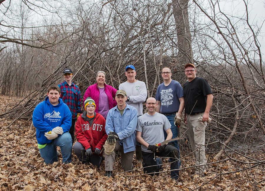 Buckthorn brigade volunteers with a pile of cleared buckthorn