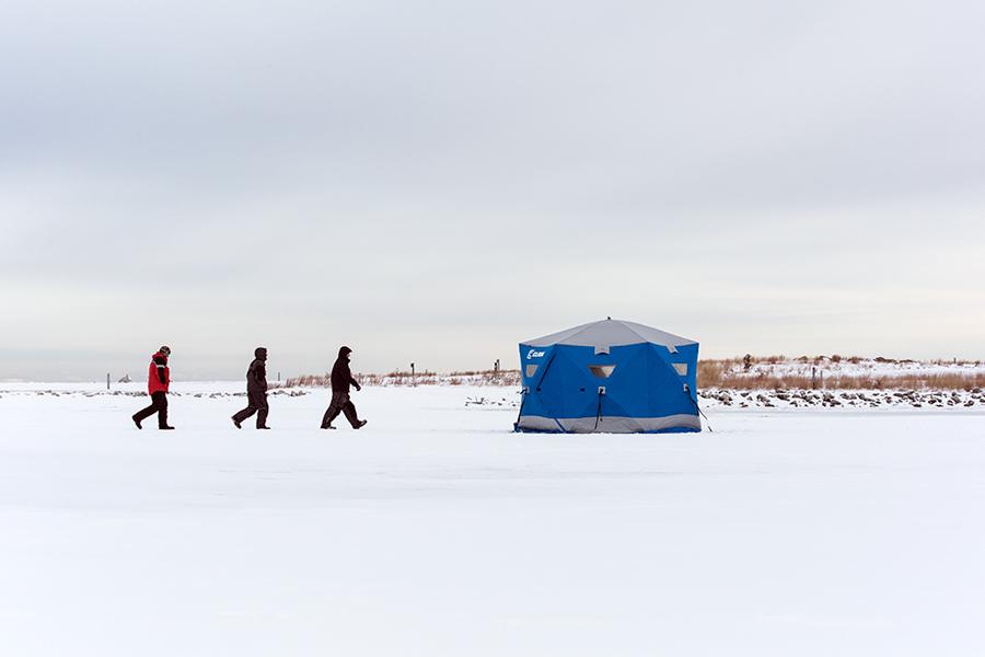 Three ice fishermen and ice fishing hut at Lakeshore State Park.