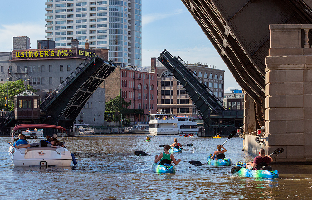a fleet of kayaks and other boats on the Milwaukee River in downtown Milwaukee.