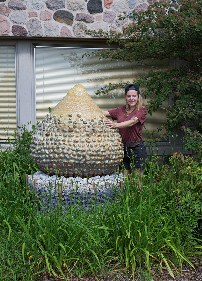 Artist Nicole Shaver with her sculpture, Geo Egg, at Forest Beach Migratory Preserve in Port Washington