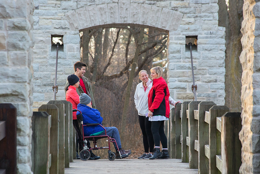 Several people, including one in a wheelchair, greeting each other on a foot bridge