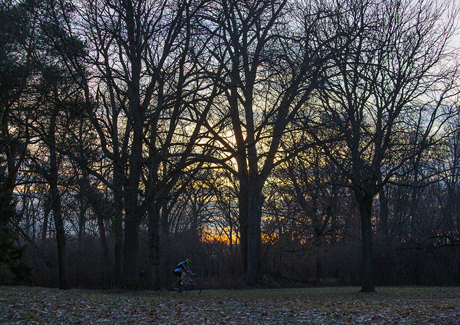 a lone cyclist riding along the Oak Leaf Trail at sunset