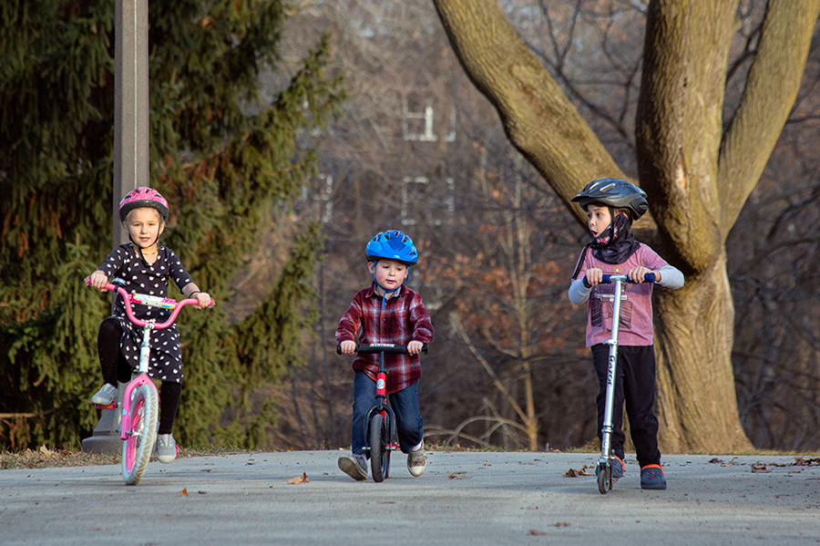 three young children, two on bikes and one on a scooter