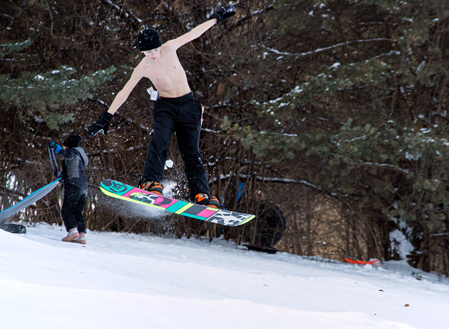 shirtless boy doing an aerial jump on a snowboard