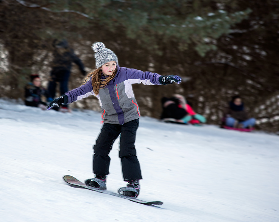 young girl on snowboard