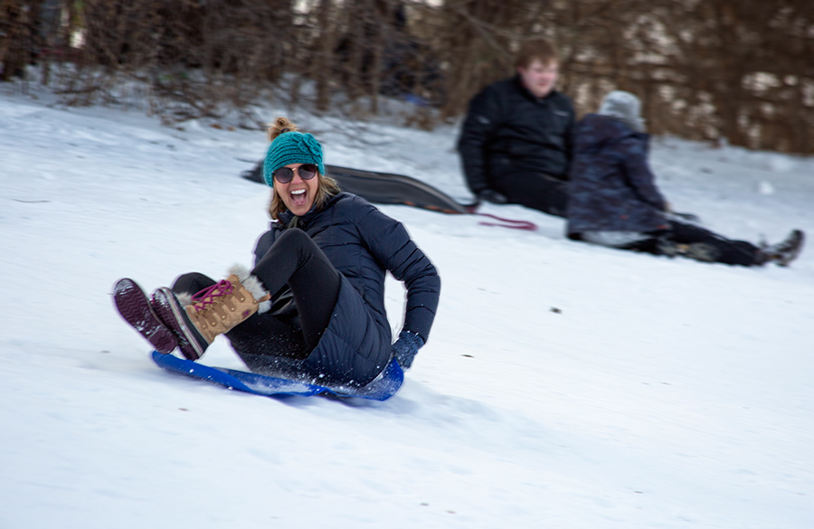young woman screaming with joy as she sleds down a hill