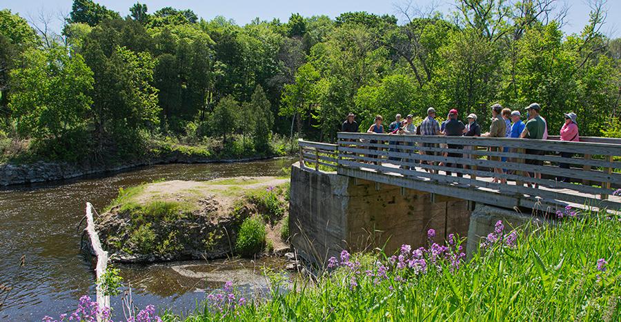 Tour group on pedestrian bridge overlooking former dam site on Milwaukee River