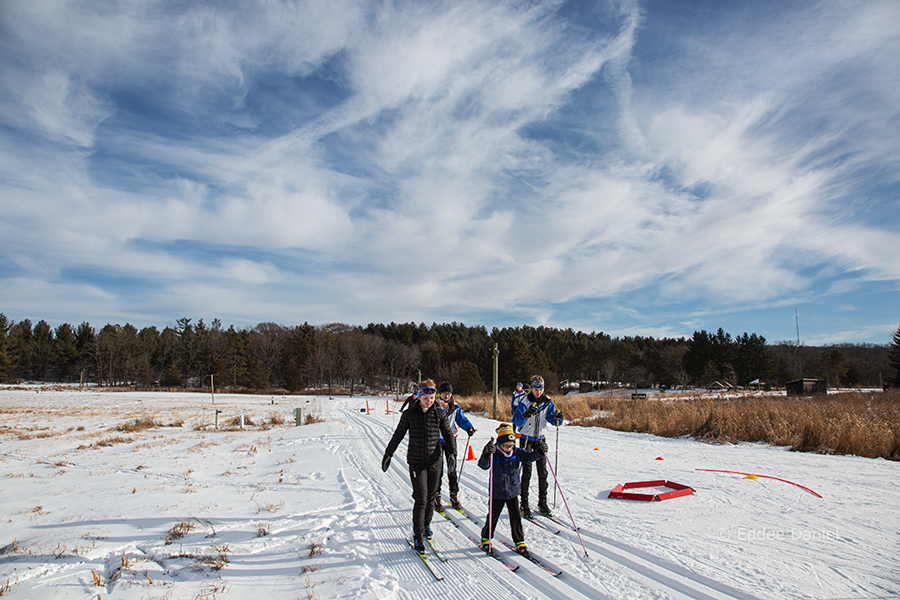 A small group of children of various ages in a skiing lesson with Lapham Peak in the background.