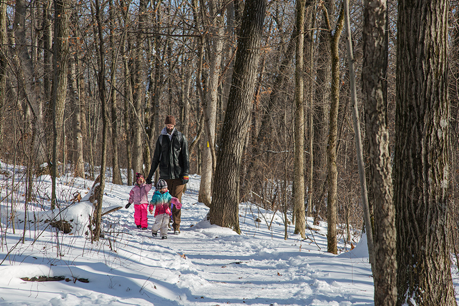 A tall man with two young girls hiking on the Ice Age Trail